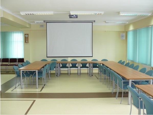 Widok Sali Konferencyjnej - rozwinięty ekran, stoły ustawione w literkę U - Kliknięcie spowoduje wyświetlenie powiększenia zdjęcia