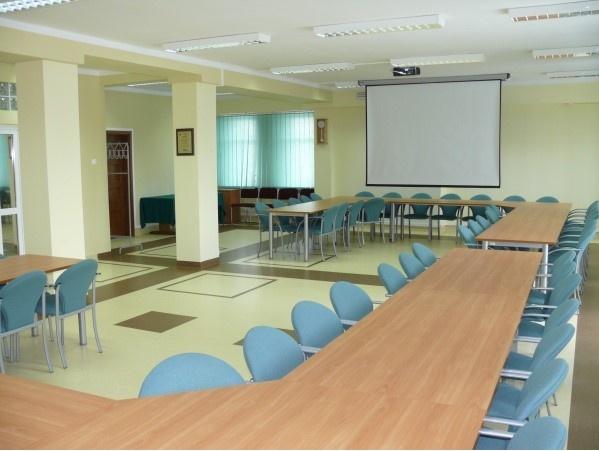 Widok na salę konfen=rencyjna pod kontem - widać rozwiniety ekran, wejście, stoły i krzesła - Kliknięcie spowoduje wyświetlenie powiększenia zdjęcia