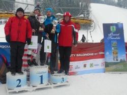 Kobieta i mężczyzna - zwycięzcy zawodów z pucharami na podium, obok wicestarosta suwalski i Wojciech Fortuna